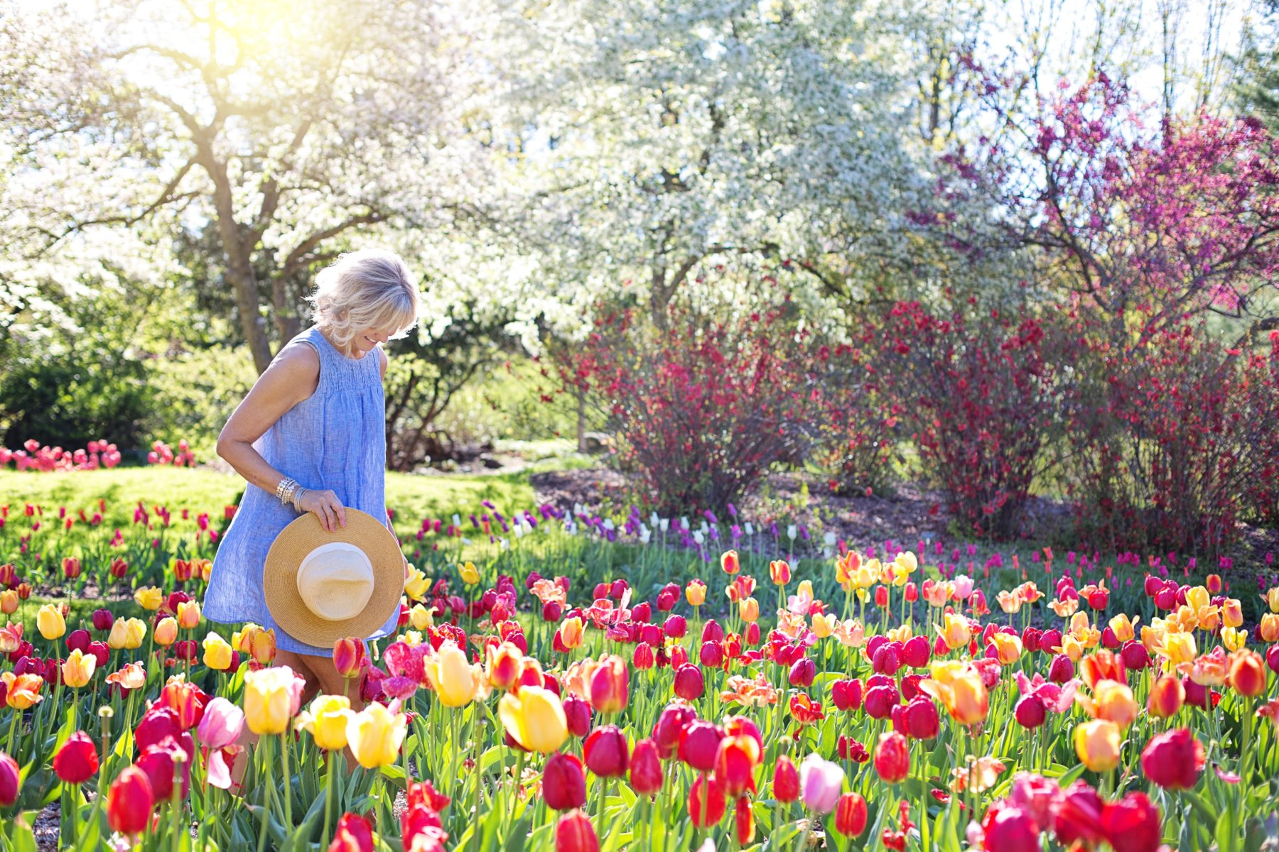 A Woman Walking Through A Flower Show Garden