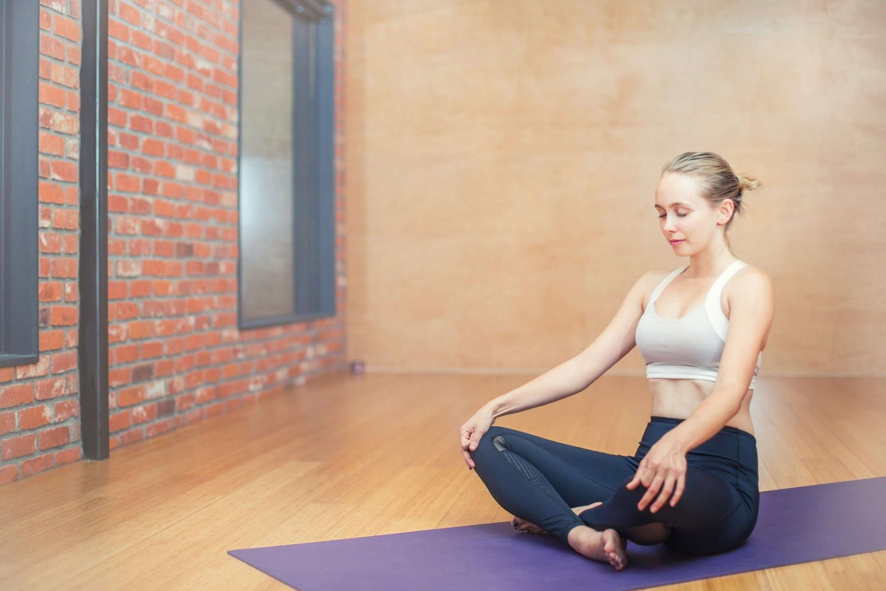 A Woman Doing Yoga While Watching Online Yoga Classes